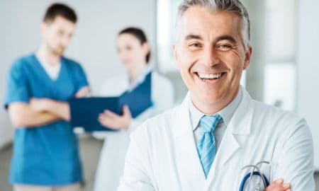A doctor smiling while hospital employees review the VueMed white paper in the background