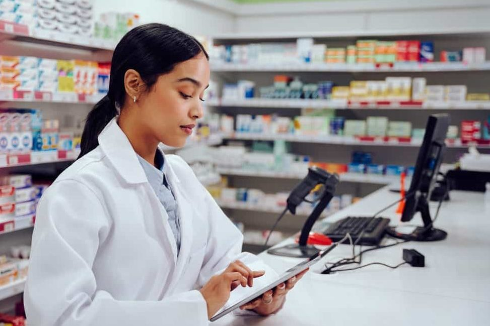 Young female pharmacist using digital tablet